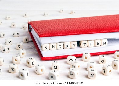 Phrase Short term written in wooden blocks in red notebook on white wooden table. Wooden abc.