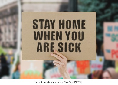 """The phrase """" Stay home when you are sick """" on a banner in hand. Human holds a cardboard with an inscription. Outbreak. Quarantine. Infection. Pandemic. Global epidemic. COVID-2019. Work. Employee"""