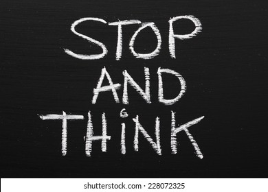 The phrase Stop and Think written on a blackboard as a reminder to take time out and work through our options before taking action