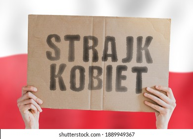 """The phrase """" Strajk Kobiet """" on a banner in men's hand with blurred Polish flag on the background. Government. Control. Illegal. Freedom. Human rights. Protest. Movement"""