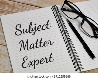 Phrase Subject Matter Expert written on notebook with pen and eye glasses on wooden table. Carrier or job concept.
