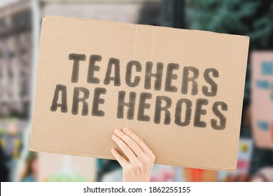 """The phrase """" Teachers are heroes  """" on a banner in men's hand with blurred background. Education. Studying. Job. Profession. Important. Essential workers"""