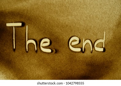"""the phrase """"the end"""" written in the sand"""
