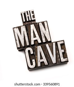 """The phrase """"The Man Cave"""" in letterpress type. Cross processed, narrow focus."""