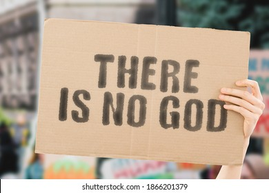 """The phrase """" There is no god """" on a banner in men's hand with blurred background. Religion. Belief. Believe. Culture. Atheism. Disagree. Untruth. Refuse"""