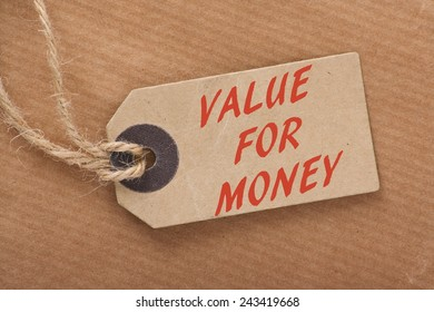 The phrase Value For Money printed on a paper price or luggage tag on a brown wrapping paper background with string