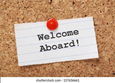 The phrase Welcome Aboard! typed onto a scrap of lined paper and pinned to a cork notice board. A phrase used to welcome a new employee or team member.