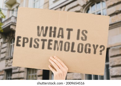 """The phrase """" What is epistemology? """" on a banner in men's hand with blurred background. Epistemic justification. Philosophy. Psychology. Mental mind. Brain. Health"""
