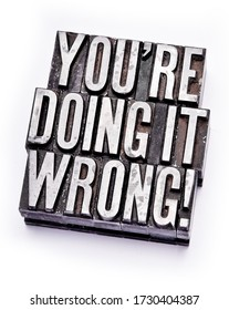"""The phrase """"You're Doing It Wrong"""" in letterpress type. Cross processed, narrow focus."""