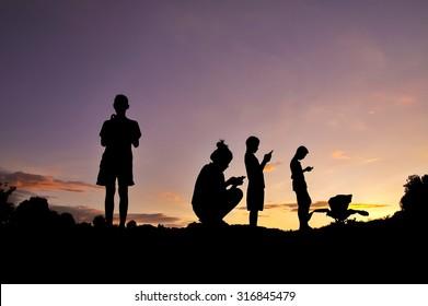 Phubbing, Silhouette of children taking smart phone at sunset