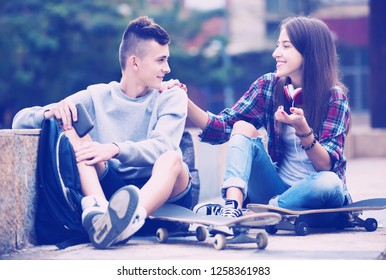 Phubbing: teenager boy and girl asking for attention in the city. Focus on boy