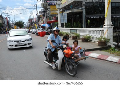 PHUKET CITY, THAILAND - OCT 12, 2013: A family ride a motorbike and sidecar through the city centre. Phuket is one of Thailand's oldest cities and is home to over 75,000 inhabitants.