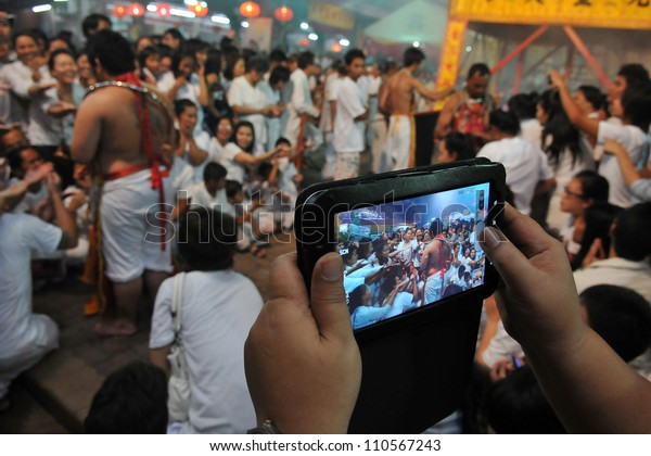 PHUKET - OCT 5: A tourist uses a tablet device to photo a ceremony at a temple during the Nine Emperor Gods Festival known locally as the Phuket Vegetarian Festival on Oct 5, 2011 in Phuket, Thailand.
