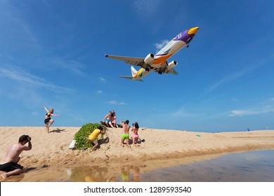 Phuket Thailand December 24, 2017 Airplane Landing over sea at Phuket Airport, Mai Khao beach phuket thailand, popular landmark tourists people come to take photo of the plane landing over tropical