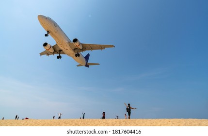 Phuket Thailand Airplane Landing over sea at Phuket Airport, Mai Khao beach phuket thailand popular landmark tourists people come to take photo of the plane landing over tropical