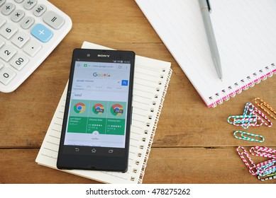 PHUKET, THAILAND, AUG 18 2016 : Mobile phone with Google app on the splite screen and old wood desk with notepad and calculator, Most of its profits are derived from AdWords