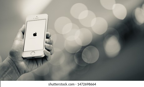 PHUKET, THAILAND - AUG 7, 2019: white apple iphone se with ios updated, holding by left hand with blurred bokeh background, apple icon and status bar on screen, black and white tone