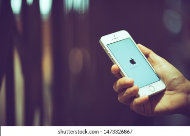 PHUKET, THAILAND - AUG 7, 2019: white apple iphone se with ios updated, holding by right hand with blurred bokeh background, apple icon and status bar on screen