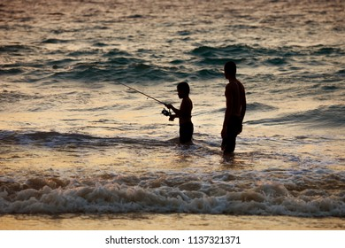 PHUKET, THAILAND - CIRCA MAR 2013: Thai fisher boy, with his father on fishing on sunset in the Andaman Sea. Thailand
