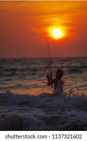 PHUKET, THAILAND - CIRCA MAR 2013: Thai fisher boy, fishing during the twilight sunset in the Andaman Sea. Thailand
