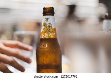 PHUKET, THAILAND - DEC 20, 2018: blurred hand reach for bottle of cold sigha beer, one of favorite thai beer, blurred light bokeh as background