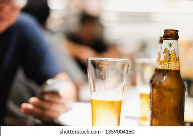 PHUKET, THAILAND - DEC 20, 2018: bottle of cold sigha beer, one of favorite thai beer, on table in restaurant, blurred people as background