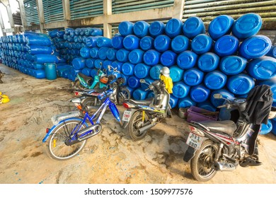 Phuket, Thailand - Dec 2017: A lot of blue plastic barrels in a warehouse waiting for a fish catch. Thai fishing flotilla preparing to receive fish. Motorcycles, mopeds, scooters of fish farm workers