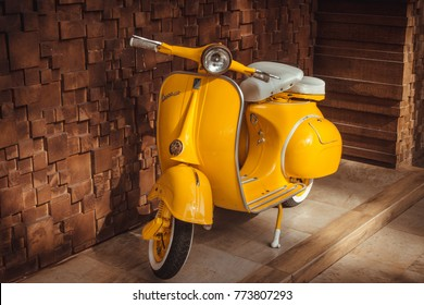 Phuket, Thailand - December 12, 2017: 1964 vintage yellow Vespa parking at the wooden wall of the restaurant. The iconic Italian designed scooter.