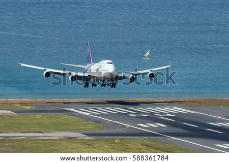 Phuket, Thailand. December 25, 2016. Thai Airways International Boeing 747-400 Landing at Runway 09 of Phuket International Airport with Sea and Sailboat Background. Copy Space for Text.