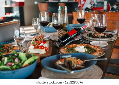 Phuket, Thailand – December 7, 2018: Festive dining table setting with traditional Italian dishes and wine served during holiday season at the restaurant in a luxury resort.