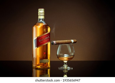Phuket, Thailand- Feb 2021. Johnnie Walker Red Label blended whisky isolated on color  background. Johnnie Walker is the most widely distributed brand of blended Scotch whisky in the world.