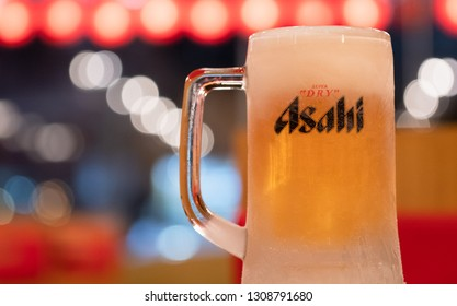 PHUKET, THAILAND - FEB 7, 2019: chilled asahi beer mug with foam on table with light bokeh, asahi is one of favorite japan beer