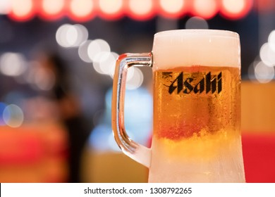 PHUKET, THAILAND - FEB 7, 2019: chilled asahi beer mug with foam on table with light bokeh and blurred waiter, asahi is one of favorite japan beer