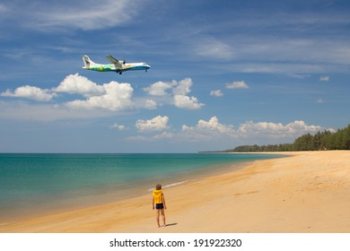 PHUKET , THAILAND- FEBRUARY 09,2013: Boy on the beach watching the landing of the aircraft of Bangkok Airways in airport of Phuket
