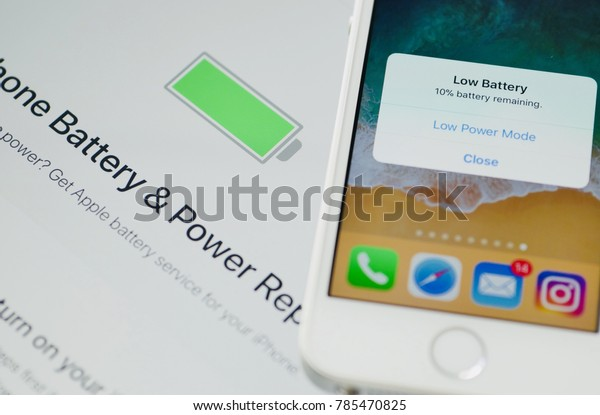 PHUKET, THAILAND - JAN 2, 2018: iphone se with low battery alert message pop up on screen, battery issue support on apple website as background, selective focus