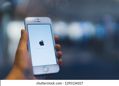 PHUKET, THAILAND - JAN 25, 2019: white apple iphone se with ios updated holding by left hand with blurred bokeh background, apple icon and status bar on screen
