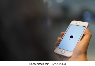 PHUKET, THAILAND - JAN 25, 2019: white apple iphone se with ios updated holding by right hand with blurred bokeh background, apple icon and status bar on screen