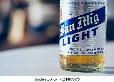 PHUKET, THAILAND - JAN 31, 2018: bottle of cold san mig light beer on white table in restaurant, blurred light bokeh as background