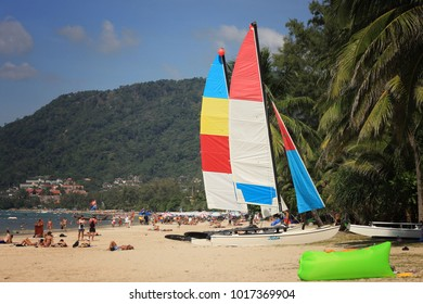PHUKET THAILAND -  January 06, 2018: Tourists from different countries are taking sunbath or playing activities and colorful boat at Patong beach, Phuket, Thailand