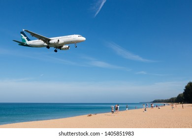 Phuket, Thailand. January 11, 2019. Silk Air Airbus A320 Reg. 9V-SLS over Mai Kao Sea Beach and Tourists on Short Final Approach for Landing at Phuket International Airport with Blue Sky.