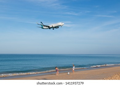 Phuket, Thailand. January 11, 2019. SilkAir Boeing 737-800 Reg.9V-MGP on Short Final Approach for Landing at Phuket International Airport with Blue Sky and Tourists who shooting fun on the beach.