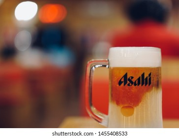 PHUKET, THAILAND - JUL 19, 2019: asahi beer mug with foam on table with light bokeh in restaurant, asahi is one of favorite japan beer
