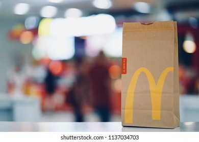 PHUKET, THAILAND - JULY 18, 2018: McDonald's brown paper bag with blurred kiosk and people in shopping mall