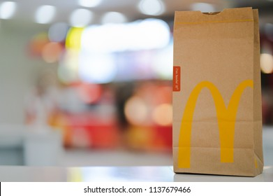 PHUKET, THAILAND - JULY 18, 2018: McDonald's brown paper bag with blurred kiosk in shopping mall