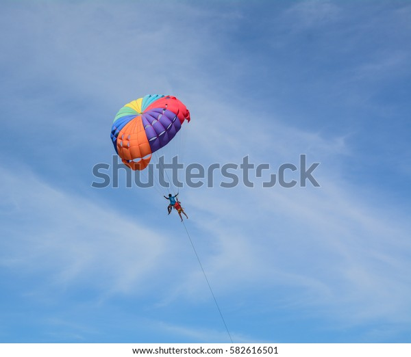 Phuket, Thailand - Jun 19, 2016. People playing parasailing in the blue sky in Phuket, Thailand. Phuket, a rainforested, mountainous island in the Andaman Sea.
