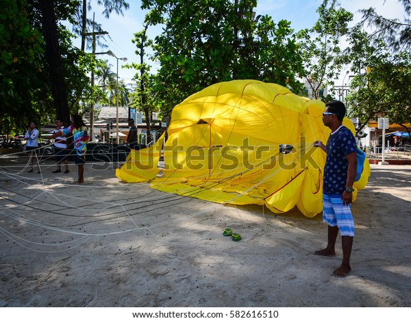 Phuket, Thailand - Jun 19, 2016. People with parasailing service on the Patong beach in Phuket, Thailand. The island is Thailands largest at 48km in length and 21km at its widest.