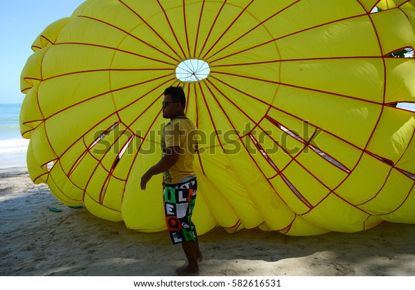 Phuket, Thailand - Jun 19, 2016. People playing parasailing on Patong beach in Phuket, Thailand. Patong is a beach resort town on the west coast of Phuket Island.