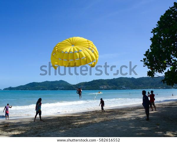 Phuket, Thailand - Jun 19, 2016. Tourists playing parasailing on Patong beach in Phuket, Thailand. Patong is a beach resort town on the west coast of Phuket Island.