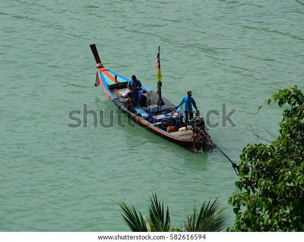 Phuket, Thailand - Jun 19, 2016. People control a motorboat on the sea in Phuket, Thailand. The island is Thailands largest at 48km in length and 21km at its widest.
