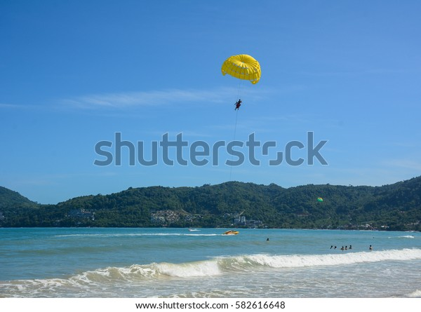 Phuket, Thailand - Jun 19, 2016. People playing parasailing in Phuket, Thailand. Phuket is home to many high-end seaside resorts, spas and restaurants.